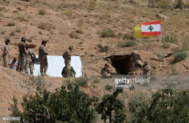 A picture taken on July 29 2017 during a tour guided by the Lebanese Shiite Hezbollah movement shows fighters standing near the Lebanese and the...