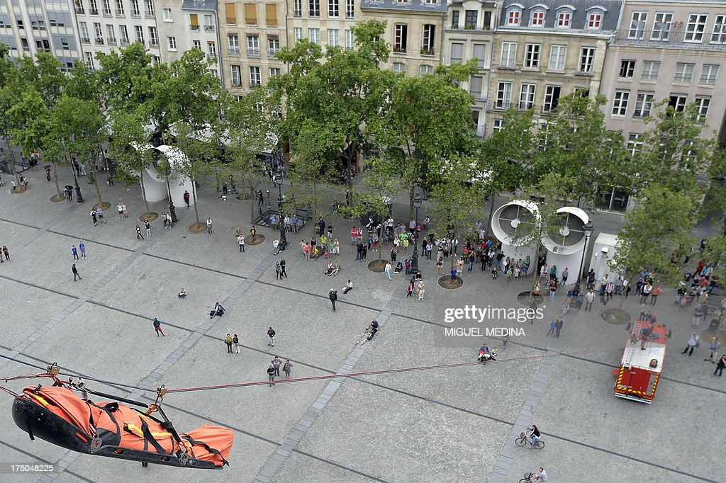 A picture taken on July 30, 2013 shows an injured evacuated during a drill from the top of the Centre Pompidou, contemporary art center, aka Beaubourg, in Paris by French firefighters from the GRIMP unit, specialized in vertical rescue operations.