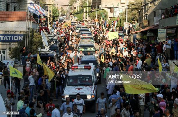 A picture taken on July 30 2017 shows an ambulance convoy of the Lebanese Shiite Hezbollah movement entering the village of alLabweh part of the...