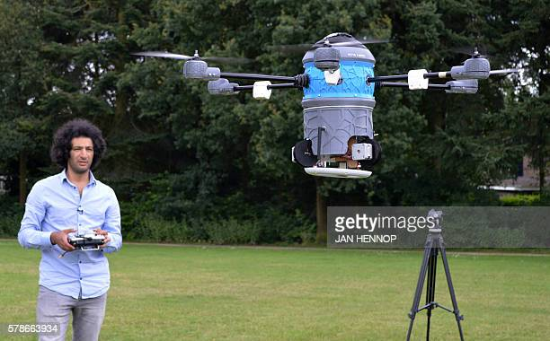 A picture taken on July 4 2016 shows Afghan refugee Massoud Hassani flying an antilandmine drone called a 'mine kafon drone' in Eindhoven Former...