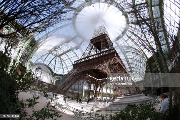 A picture taken on July 4 2017 shows a replica of the Eiffel Tower as part of the set for the Chanel 20172018 fall/winter Haute Couture collection at...