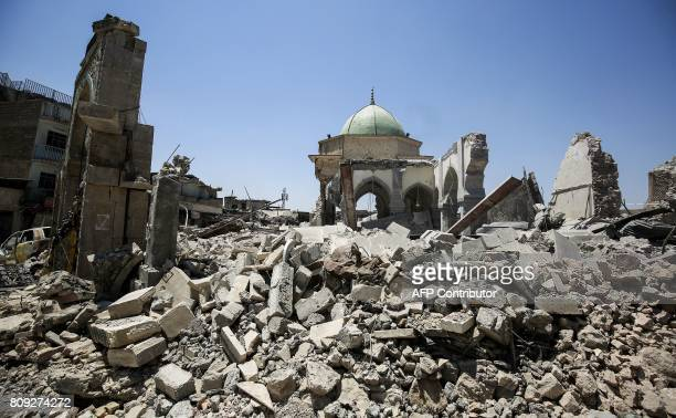 A picture taken on July 5 2017 shows the rubble outside and the exterior of the destroyed AlNuri Mosque and its gate in the Old City of Mosul during...