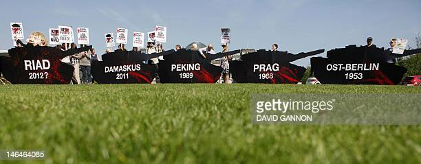 FILES Picture taken on July 6 2011 shows demonstrators holding a protest with mockup tanks in front of the Reichstag the building which houses the...