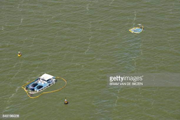 A picture taken on July 6 2016 shows an aerial view of a sunk Belgian boat on the Ijsselmeer few miles away from Stavoren The reason of the drift is...