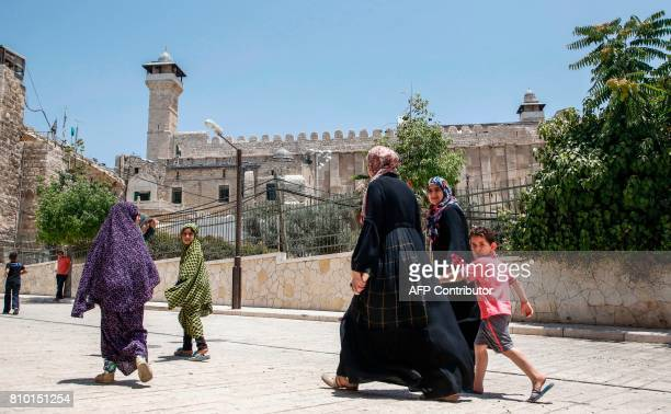 A picture taken on July 7 2017 shows Palestinians walking by outside the Cave of the Patriarchs also known as the Ibrahimi Mosque which is a holy...