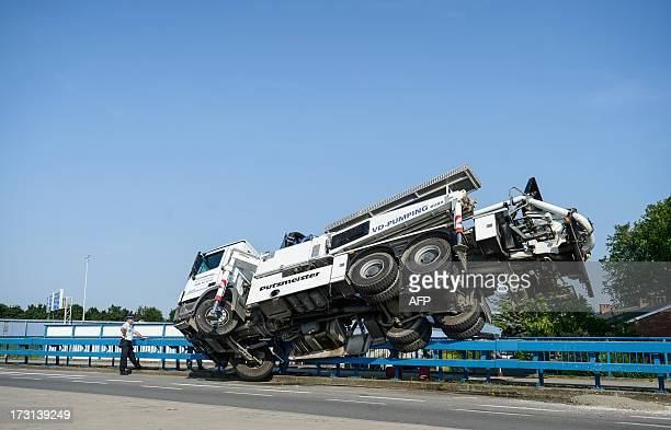 A picture taken on July 8 2013 shows a tilted concrete mixer truck on a bridge threatening to fall on the railway track at the Route de Lennik /...