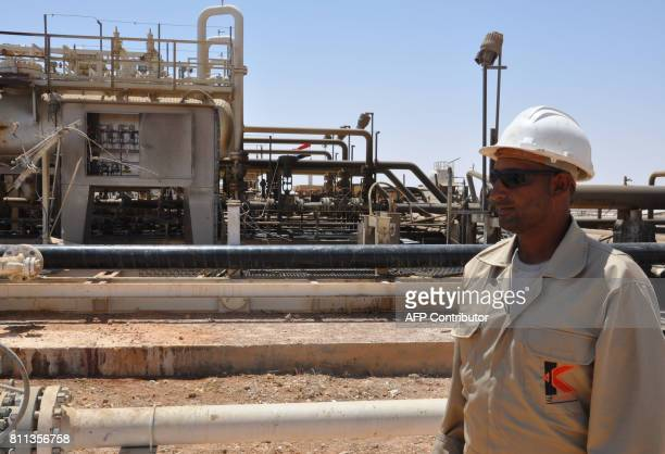 A picture taken on July 9 2017 shows an employee standing at Syria's Arak gas field 35 kilometres northeast of the ancient city of Palmyra in the...