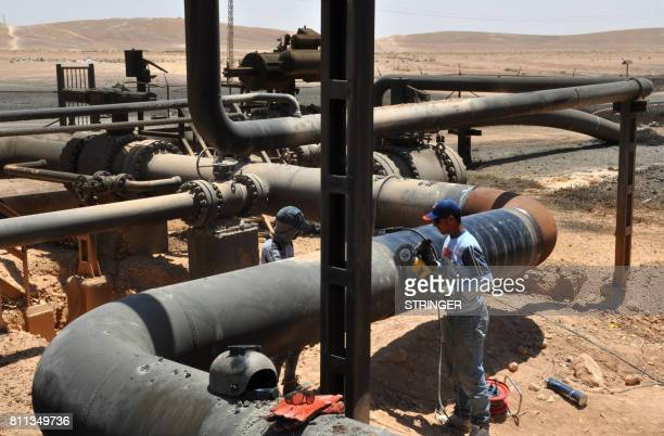 A picture taken on July 9 2017 shows workers at Syria's Arak gas field 35 kilometres northeast of the ancient city of Palmyra in the central province...