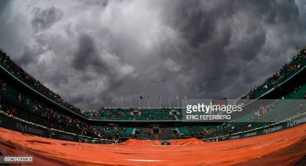 A picture taken on June 06 2017 in Paris shows the Philippe Chatrier court being covered by a tarp during a downpour at the Roland Garros 2017 French...