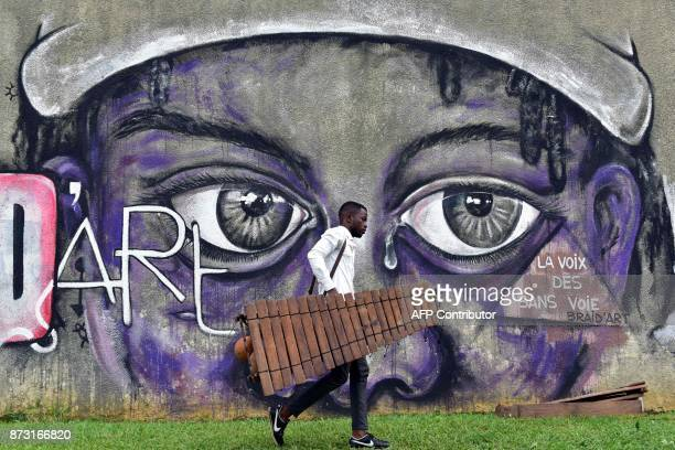 A picture taken on June 1 2017 shows a student walking with a balafon a wooden xylophon in the courtyard of the National Higher Institute of Arts and...