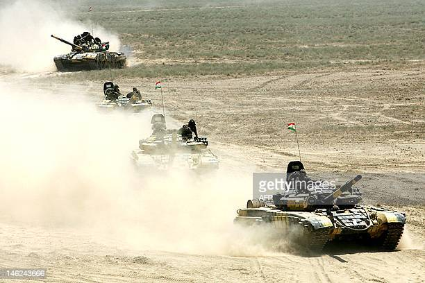 A picture taken on June 10 2012 shows Russianbuilt tanks rolling under Tajikistan's flags during Peace Mission 2012 joint counterterrorism military...