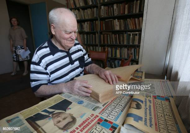 A picture taken on June 12 2017 shows a blind man reading a braille book on a table covered with local newspapers in Donetsk At the offices of the...
