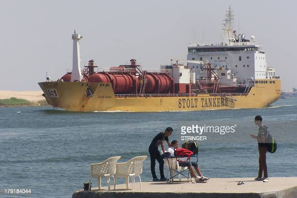 A picture taken on June 13 2013 shows a tanker ship sailing through the Suez Canal near the port city of Ismailia in Egypt A container ship in the...