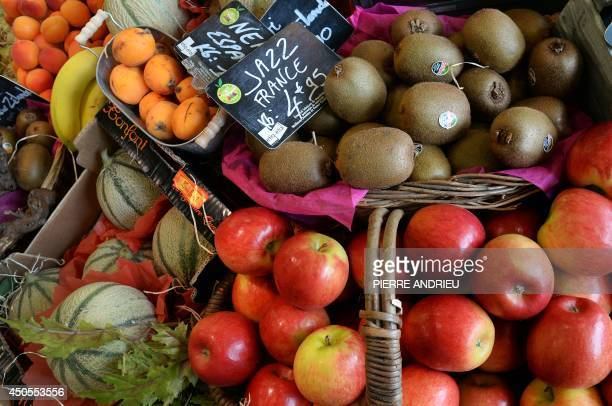 A picture taken on June 13 2014 shows apricots bananas melons kiwis and apples in a local business in Paris AFP PHOTO / PIERRE ANDRIEU
