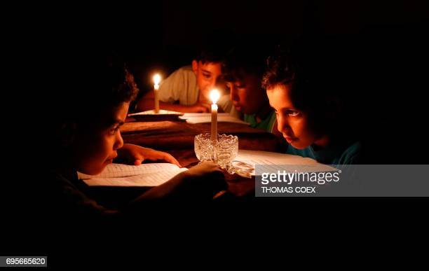 TOPSHOT A picture taken on June 13 shows Palestinian children at home reading books by candle light due to electricity shortages in Gaza City Israeli...