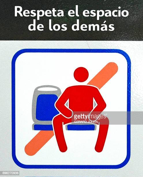 A picture taken on June 15 2017 in a bus of Madrid Municipal Transport company shows a new pictogram against manspreading An antimanspreading...