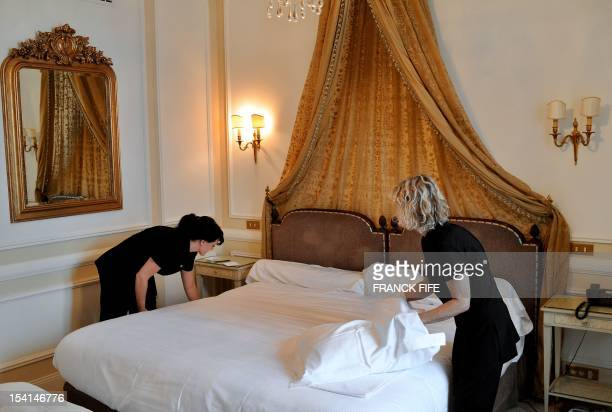 A picture taken on June 15 shows chambermaids making the bed in a room of the luxury hotel 'Hotel du Palais' in Biarritz Southwestern France This...