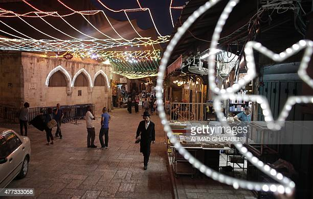A picture taken on June 16 2015 shows an ultra Orthodox Jewish man walking as fairy lights decorate a shop near the entrance of the AlAqsa mosque...
