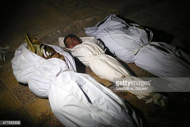 A picture taken on June 16 2015 shows the wrapped bodies of victims including a baby lying on the ground outside a morgue due to the lack of space...