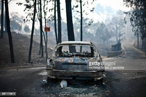 A picture taken on June 18 2017 shows a burnt car on a road after a wildfire in Pedrogao in central Portugal A wildfire in central Portugal killed at...