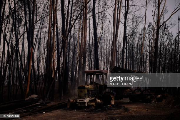 A picture taken on June 18 2017 shows a burnt vehicle after a wildfire near the village of Castanheira de Pera Portugal declared three days of...
