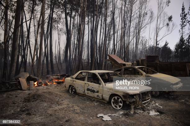 A picture taken on June 18 2017 shows burnt cars in an area devastated by a wildfire near Castanheira de Pera Portugal declared three days of...