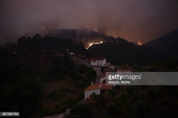 A picture taken on June 18 2017 shows flames and smoke during a wildfire near the village of Mega Fundeira Portugal declared three days of national...