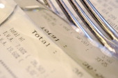 A picture taken on June 20 2012 at a restaurant in Quimper western France shows fork and knife on an invoice indicating the two Valueadded tax 70 and...