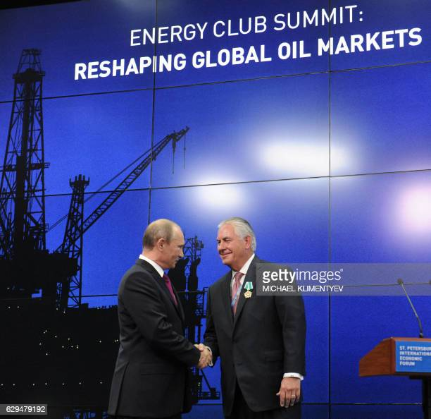 A picture taken on June 21 2013 shows President Vladimir Putin and ExxonMobil Chairman and CEO Rex W Tillerson at a ceremony to present awards to the...