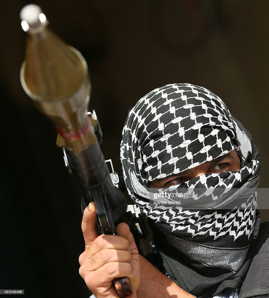 A picture taken on June 21, 2014 in the Iraqi town of Taza Khurmatu, shows a Shiite Turkman fighter from the so-called Sahwa or 'Awakening' force, manning a position on the front line with insurgents led by the jihadist Islamic State of Iraq and the Levant (ISIL) group which has overran swathes of five provinces north and west of Baghdad. In this Iraqi town, a motley brigade of Shiite Turkmen locals adjust their weapons and headscarves before heading out to defend their homes from encroaching Sunni militants.