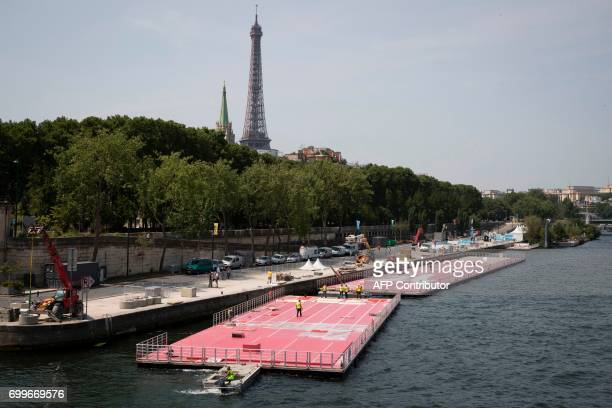 TOPSHOT A picture taken on June 22 2017 in Paris shows an athletics track being installed on the Seine river / AFP PHOTO / JOEL SAGET