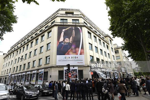 A picture taken on June 23 2015 in Paris shows a giant placard displayed on the wall reading 'Our ambition Olympic and Paralympic ' marking the...
