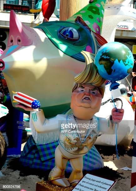 A picture taken on June 24 2017 shows a 'hoguera' representing US President Donald Trump holding a rocket and and Earthshaped airballoon during the...