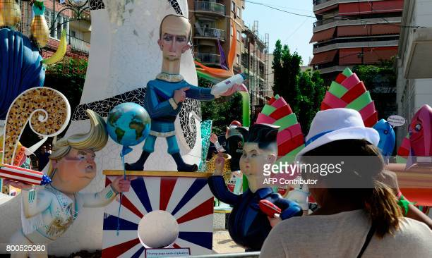A picture taken on June 24 2017 shows a 'hoguera' representing US President Donald Trump holding a rocket and and Earthshaped airballoon next to...