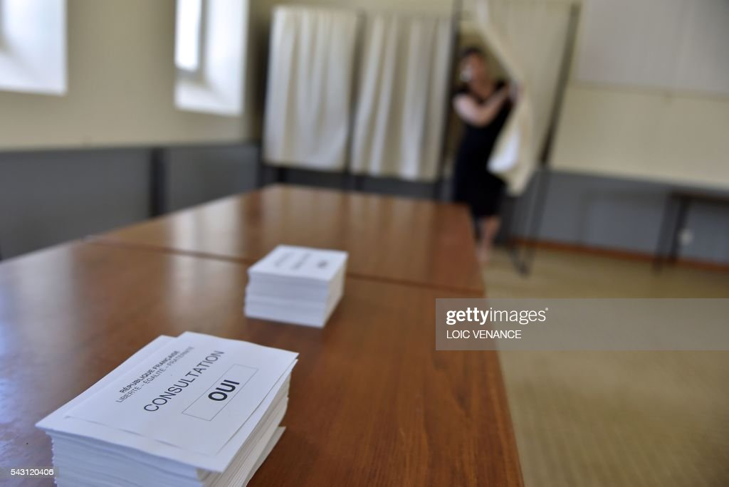 A picture taken on June 26, 2016 shows ballot papers on a table as a woman comes out of a polling booth in Notre-Dame-des-Landes during a local referendum organised in Loire-Atlantique on subject of the Notre-Dame-des-Landes' airport project. Nearly One million people living in France's Loire-Atlantique department are voting in a referendum which poses the question 'Are you in favour of the project to transfer the Nantes-Atlantique airport to the municipality of de Notre-Dame-des-Landes?' to voters. The referendum was organised by the French executive power hoping to find a solution to the issue which has dragged on for 50 years. / AFP / LOIC