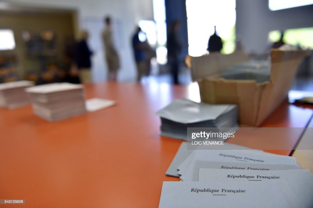 A picture taken on June 26, 2016 shows ballot papers on a table as people queue to cast their vote in Notre-Dame-des-Landes during a local referendum organised in Loire-Atlantique on subject of the Notre-Dame-des-Landes' airport project. Nearly One million people living in France's Loire-Atlantique department are voting in a referendum which poses the question 'Are you in favour of the project to transfer the Nantes-Atlantique airport to the municipality of de Notre-Dame-des-Landes?' to voters. The referendum was organised by the French executive power hoping to find a solution to the issue which has dragged on for 50 years. / AFP / LOIC