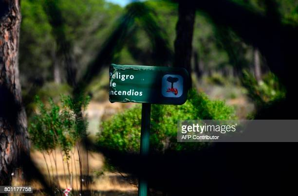 A picture taken on June 26 2017 shows a warning safety sign reading 'Fire hazard' at the visitor centre El Acebuche next to Mazagon after a wildfire...