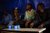 A picture taken on June 27 2013 shows a group of Kenyan men sitting in a drinking den in the Mathare slum of Nairobi Chang'aa is a potent illegal...