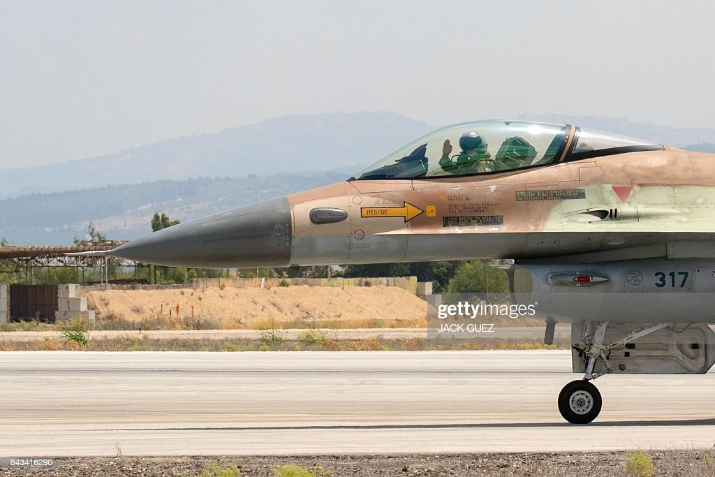 A picture taken on June 28, 2016 shows an Israeli pilot waving from the cockpit of his F-16 fighter jet before taking off at the Ramat David Air Force Base, located in the Jezreel Valley, southeast of the Israeli port city of Haifa. / AFP / JACK
