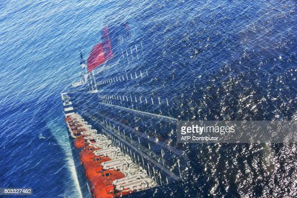 TOPSHOT A picture taken on June 28 2017 shows a reflection on a glass window against the Atlantic ocean of the Cunard cruise liner RMS Queen Mary 2...