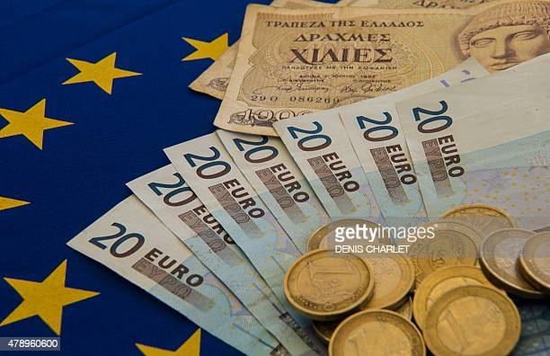 A picture taken on June 29 2015 in Lille shows Drachma bills Greece's former currency next to euro bills and coins The European single currency...