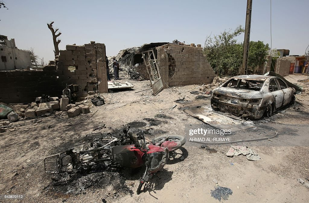 A picture taken on June 30, 2016 shows leftovers of damaged vehicles in the city of Fallujah following battles between Iraqi pro-government forces and Islamic State (IS) group jihadists. Iraqi forces have retaken full control of Fallujah, a longtime jihadist bastion just 50 kilometres (30 miles) west of Baghdad, after a vast operation that was launched in May. / AFP / AHMAD