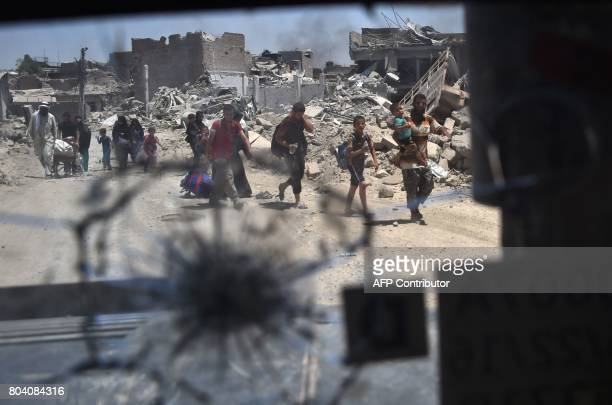 A picture taken on June 30 2017 through a broken humvee windshield shows Iraqis evacuating the Old City of Mosul as the Iraqi forces push their...