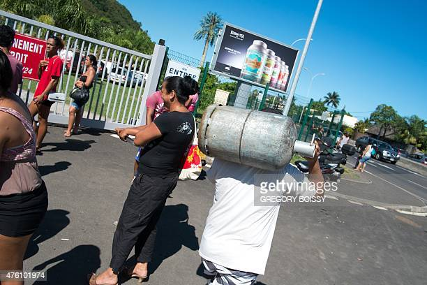 LEYRAL A picture taken on June 5 2015 shows a man holding a gas bottle on his shoulders while people wait for a gas distribution in front of the SDA...