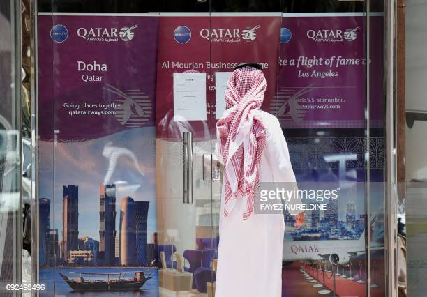 A picture taken on June 5 2017 shows a man standing outside the Qatar Airways branch in the Saudi capital Riyadh after it had suspended all flights...