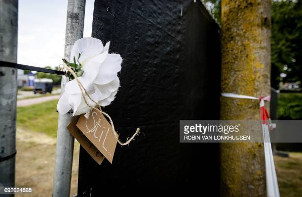 A picture taken on June 5 2017 shows a white flower and a note reading 'silent' after a 14yearold girl was found in a ditch on the edge of the De...