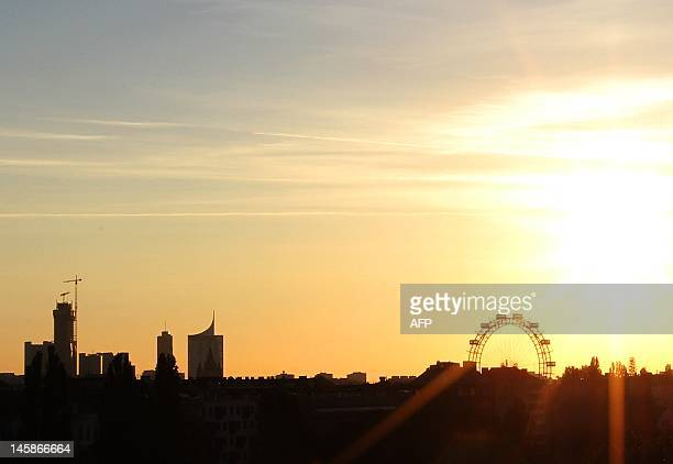 A picture taken on June 6 2012 shows the Ferris wheel of the Prater amusement park and cranes at the construction site of the Vienna DC towers which...