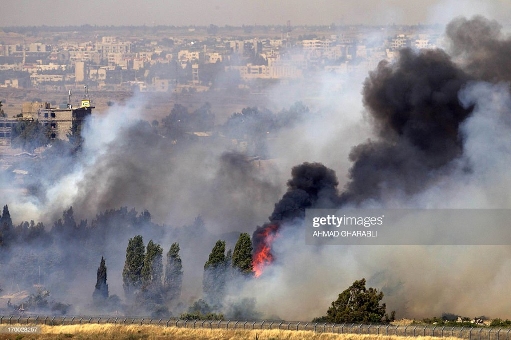 A picture taken on June 6, 2013 from the Israeli side along the Israel-Syria ceasefire line in the Golan Heights shows smoke billowing from a fire caused by clashes between Syrian rebels and forces loyal to the regime near the Quneitra crossing. Syrian regime forces retook the only crossing point along the ceasefire line after it was seized earlier by rebels, an Israeli security source said. The crossing is seen as strategically important because of its position in a demilitarised zone of the Golan Heights, most of which Israel seized from Syria in the 1967 Six-Day War. AFP PHOTO / AHMAD GHARABLI