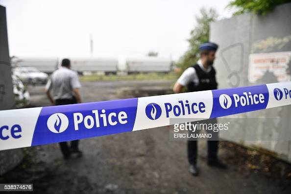 A picture taken on June 6 2016 shows Belgian police officers standing guard behind a security cordon set up at the scene of a collision which...