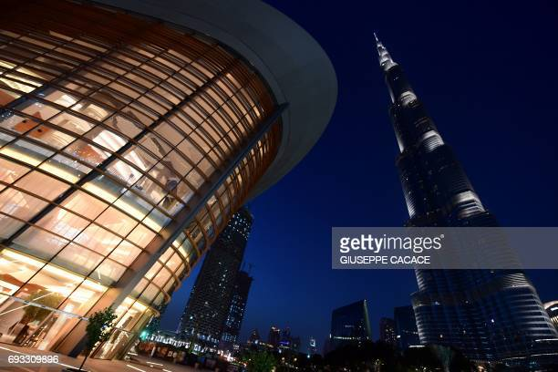 TOPSHOT A picture taken on June 6 2017 shows a general view of the exterior of the Dubai Opera with the Burj Khalifa nearby in downtown Dubai in the...